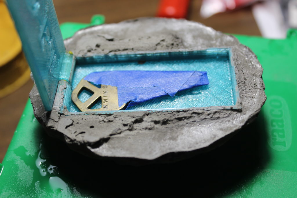 A cast key rock with light blue key box and a key covered in tape.